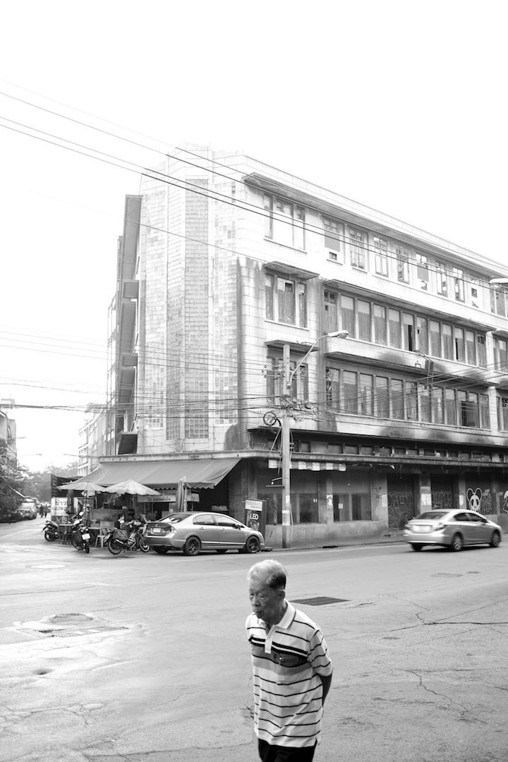 A man walking by (strideby) a building in Bangkok's China Town District in the background