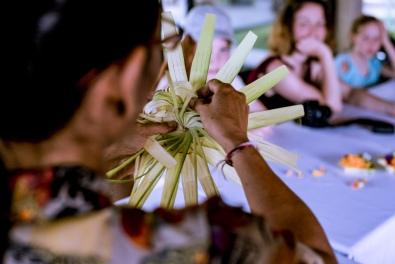 A Balinese woman teaching tourists how to make canang sari - Bali Street Photographer