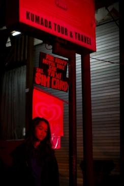 Model Immanuela poses outside Pasar Ubud at night exhibited by Don't Take Pictures - Bali Street Photographer