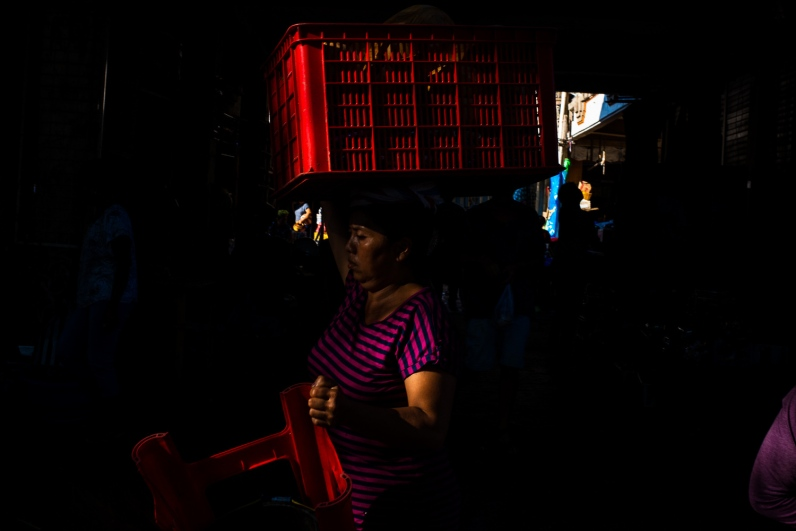 Woman carying a basket at Pasar Ubud exhibited by Don't Take Pictures - Bali Street Photographer
