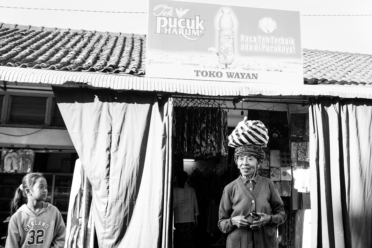 A young Balinese girl next to an elderly Balinese woman - Bali Street Photographer on the Road