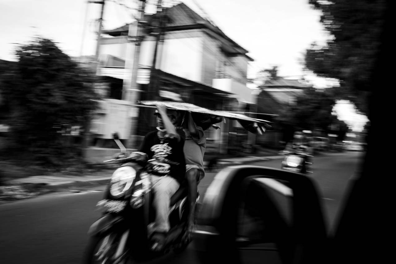 Two young adults carrying a kite on a scooter near Ubud Bali July 2020