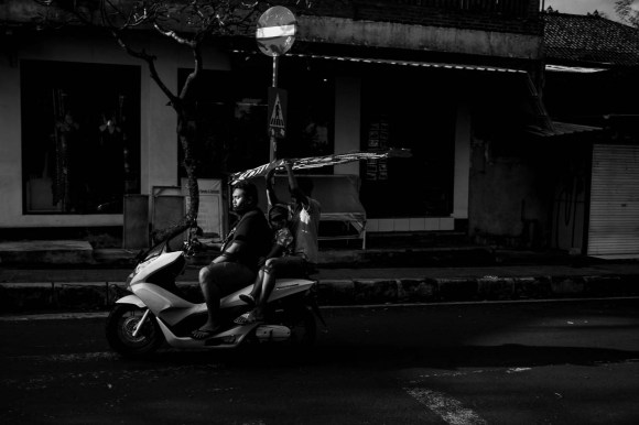 Kite season - a father and his two boys transporting their kite on a scooter in Ubud Bali